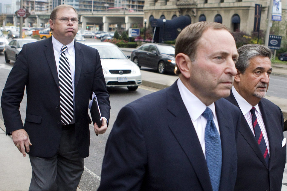Photo -   Craig Leipold, left, owner of Minnesota Wild, follows NHL Commissioner Gary Bettman, center, and Washington Capitals owner Ted Leonsis, right, leaves the NHLPA's following collective bargaining in Toronto on Thursday, Oct. 18, 2012. (AP Photo/The Canadian Press, Chris Young) offices with