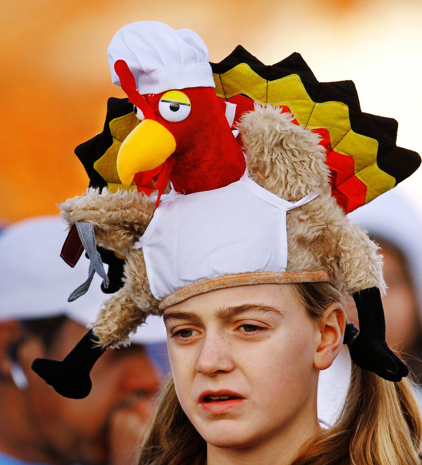 Photo - Katie Andrews, 12, wears an elaborate turkey hat as she waits for the 5K run to start during the annual Turkey Trot in downtown Edmond Thursday morning,  Nov. 24, 2011.  Andrews , who lives in Arkansas, is in Edmond visiting her grandparents for the holiday.  This was her first  time to participate in the Turkey Trot. Photo by Jim Beckel, The Oklahoman