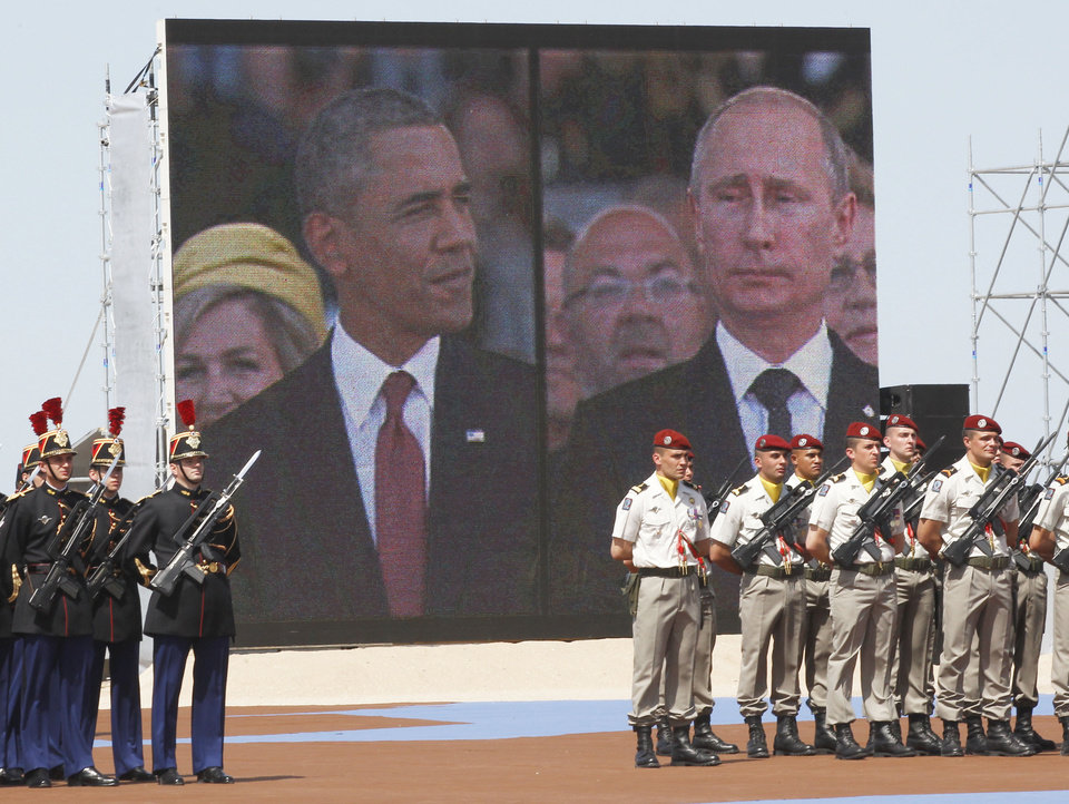 Photo - A large screen shows a picture of  Russian President Vladimir Putin, right, and U.S. President Barack Obama during the commemoration of the 70th anniversary of the D-Day in Ouistreham, western France, Friday, June 6, 2014. World leaders and veterans gathered by the beaches of Normandy on Friday to mark the 70th anniversary of World War Two's D-Day landings. (AP Photo/Christophe Ena, Pool)