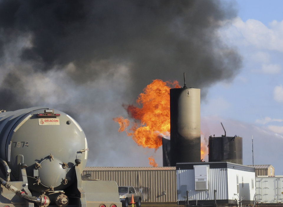 Photo - In this Monday, July 7, 2014 photo, a saltwater disposal facility burns after being hit by lightning near Alexander, N.D. In just over a month, lightning strikes have destroyed three of the state's more than 440 saltwater disposal facilities. Saltwater is a byproduct of oil production. (AP Photo/Josh Wood)