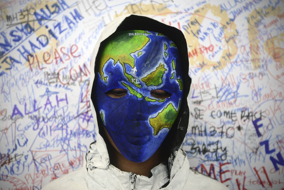 Photo - An unidentified woman with her face painted, depicting the flight of the missing Malaysia Airline, MH370, poses in front of the