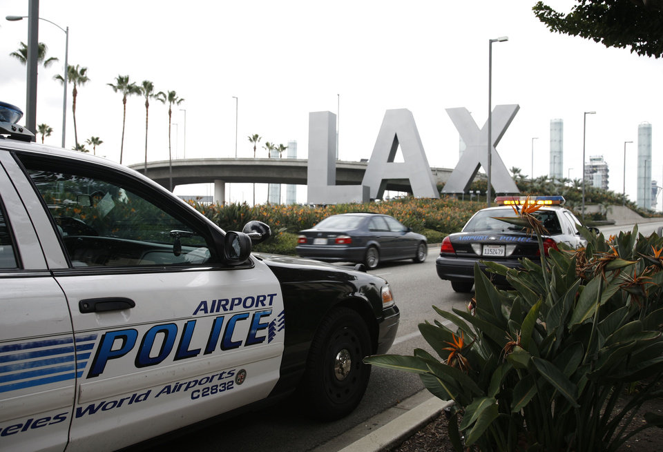 Photo -   FILE - In a Dec. 26, 2009 file photo, airport police monitor the entrance of Los Angeles International Airport in Los Angeles. Yongda Huang Harris, 28, flying from Japan to Boston, was arrested Friday, Oct. 5, 2012, during a stopover at Los Angeles International Airport, wearing a bulletproof vest and flame-resistant pants, and travelling with a suitcase full of weapons, leg irons, a smoke grenade, a gas mask and a biohazard suitd, U.S. Immigration and Customs Enforcement officials said Tuesday, Oct. 10, 2012. (AP Photo/Jason Redmond, File)
