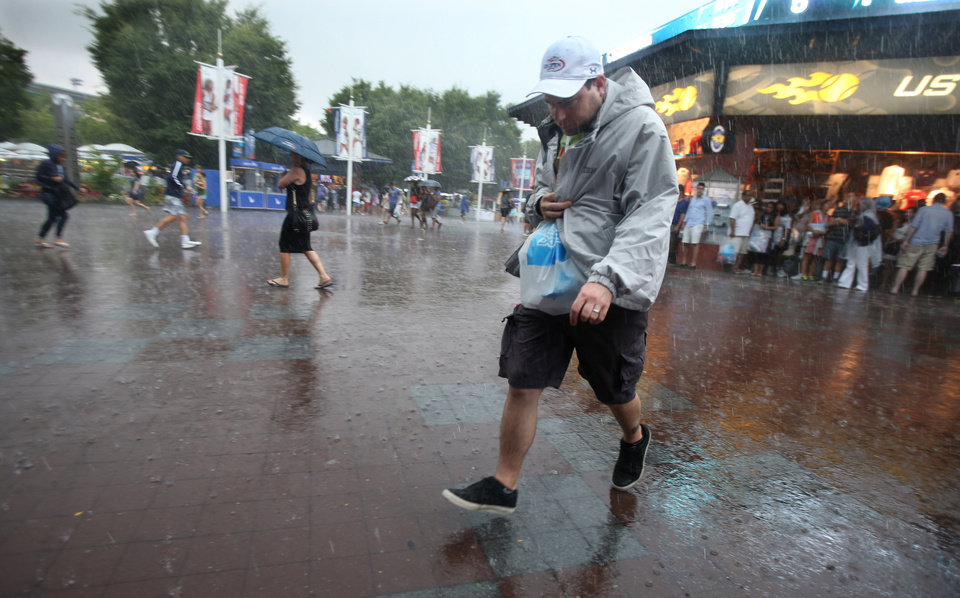 Photo - Tennis fans look for cover from a steady rain falling on the Billie Jean King National Tennis Center suspending play at  the 2014 U.S. Open tennis tournament, Sunday, Aug. 31, 2014, in New York. (AP Photo/John Minchillo)