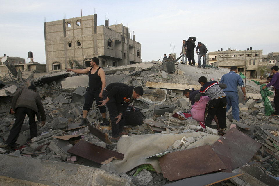 Palestinians inspect the rubble of the destroyed house of Hamas militant Mohammad Abu Shmala, following an Israeli air strike in Rafah, southern Gaza Strip, Friday, Nov. 16, 2012.(AP Photo/Eyad Baba) ORG XMIT: JRL141