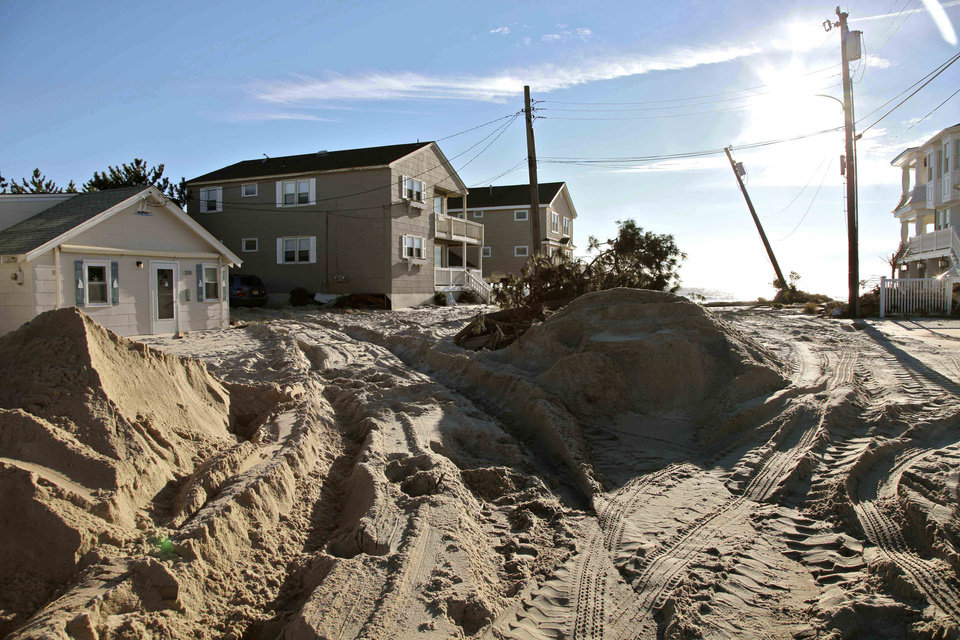 Sand washed inland by superstorm Sandy is piled on the streets of Spray beach, N.J. on Thursday, Nov. 1, 2012. Sandy, the storm that made landfall Monday, caused multiple fatalities, halted mass transit and cut power to more than 6 million homes and businesses. (AP Photo/Robert Ray)