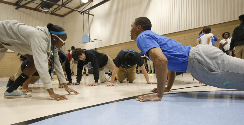 Photo - The Thunder's Russell Westbrook does push-ups with a group of students as several of the players join 60 middle school students in a Thunder Fit clinic, presented by Homeland, at Webster Middle School in Oklahoma City, OK, Tuesday, January 13, 2015,  Photo by Paul Hellstern, The Oklahoman