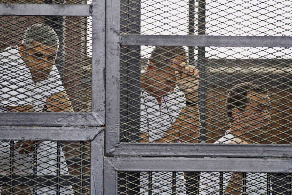 Photo - FILE - In this Thursday, May 15, 2014 file photo, from left, Mohammed Fahmy, Canadian-Egyptian acting bureau chief of Al-Jazeera, Australian correspondent Peter Greste, and Egyptian producer Baher Mohamed appear in a defendant's cage along with several other defendants during their trial on terror charges at a courtroom in Cairo. Egyptian Judge Mohamed Nagui Shehata has sentenced the three journalists to seven years in prison Monday, June 23, 2014 in their trial on terrorism-related charges. (AP Photo/Hamada Elrasam, File)