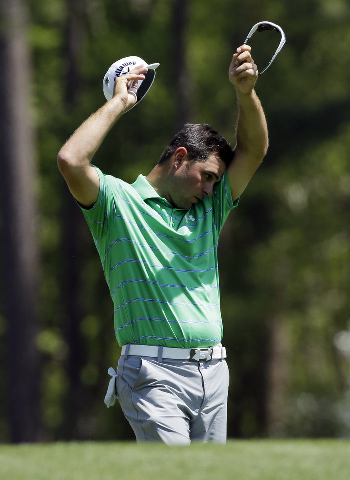 Photo - Gary Woodland wipes his brow before teeing off on the12th hole landed in the water during the third round of the Masters golf tournament Saturday, April 12, 2014, in Augusta, Ga. (AP Photo/David J. Phillip)