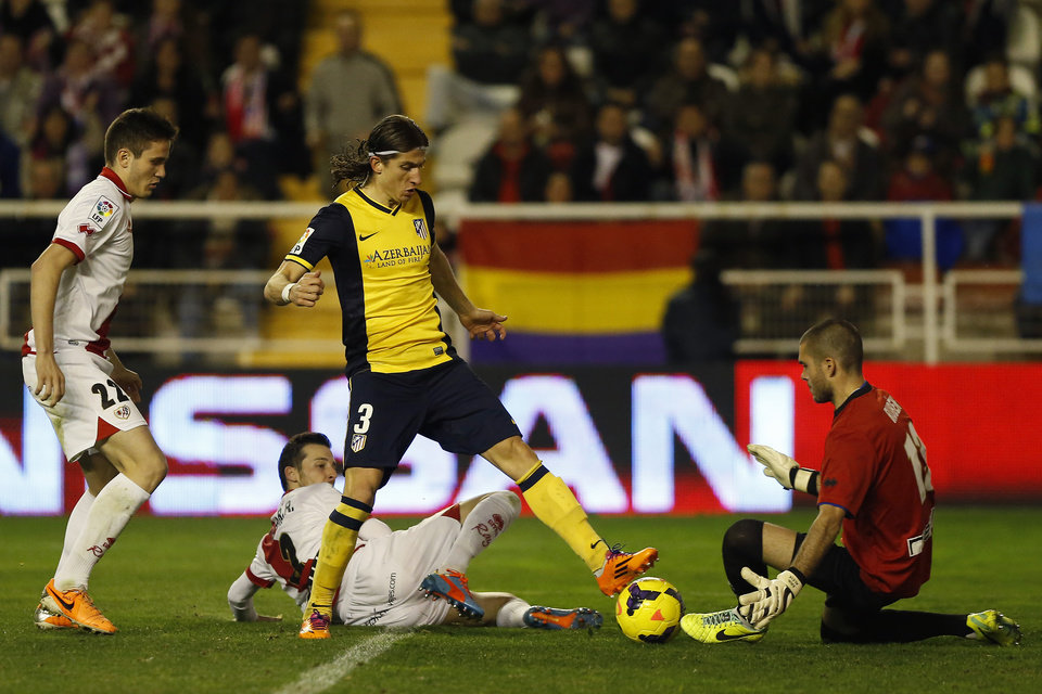Photo - Atletico's Filipe Luis, second right, in action with Rayo's goalkeeper Ruben, right, during Spanish La Liga soccer match between Rayo Vallecano and Atletico de Madrid at the Vallecas stadium in Madrid, Spain, Sunday, Jan. 26, 2014. (AP Photo/Andres Kudacki)