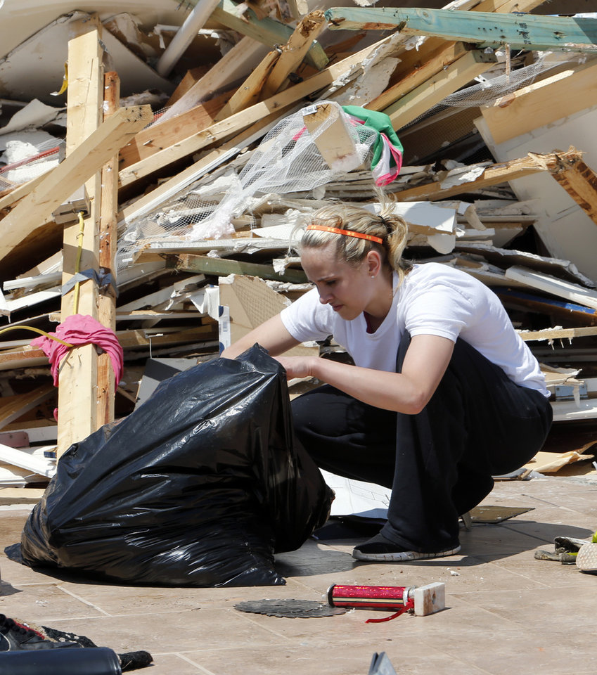 Photo - Cheyenne Wiley, 18, sorts through items gathered from the remains of her home on Thursday, May 23, 2013 in Little Axe, Okla.  The house was destroyed in Sunday's tornado in the Woodlands and Pecan Valley area.  Cheyenne lost all her clothes and her cap and gown for her graduation on Tuesday.   Photo by Steve Sisney, The Oklahoman