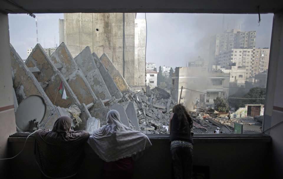 Photo - A Palestinian family looks from a window to the rubble of the collapsed 15-story Basha Tower following early morning Israeli airstrikes in Gaza City, Tuesday, Aug. 26, 2014. Israel bombed two Gaza City high-rises with dozens of homes and shops Tuesday, collapsing the 15-story Basha Tower and severely damaging the Italian Complex in a further escalation in seven weeks of cross-border fighting with Hamas. (AP Photo/Khalil Hamra)