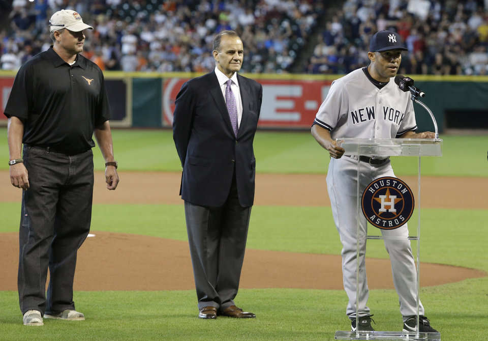 Photo - Former New York Yankees pitcher Roger Clemens, left, and former Yankees manager Joe Torre, center, listens as relief pitcher Mariano Rivera, right, gives remarks during a presentation ceremony before a baseball against the Houston Astros game Sunday, Sept. 29, 2013, in Houston. Rivera is retiring after 18 years in baseball. (AP Photo/Richard Carson)