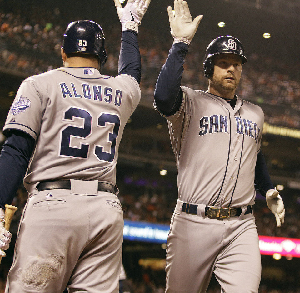 Photo -   San Diego Padres' Chase Headley, right, is congratulated by Yonder Alonso (23) after hitting a home run off San Francisco Giants' Ryan Vogelsong in the fourth inning of a baseball game on Friday, Sept 21, 2012, in San Francisco. (AP Photo/Ben Margot)