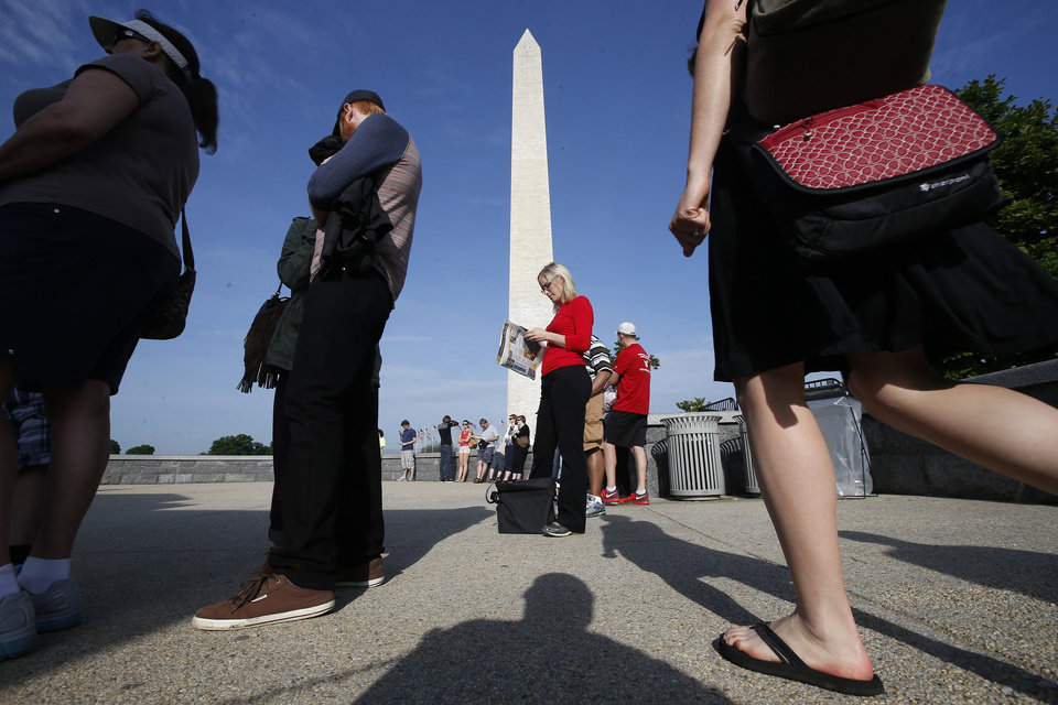 Photo - Visitors line up for tickets which are distributed at on a first-come basis at the Washington Monument in Washington, Monday, May 12, 2014, ahead of a ceremony to celebrate its re-opening. The monument, which sustained damage from an earthquake in August 2011, is reopening to the public today. (AP Photo)