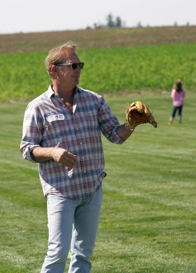 Photo - Actor Kevin Costner  plays catch during a party celebrating the 25th anniversary of the