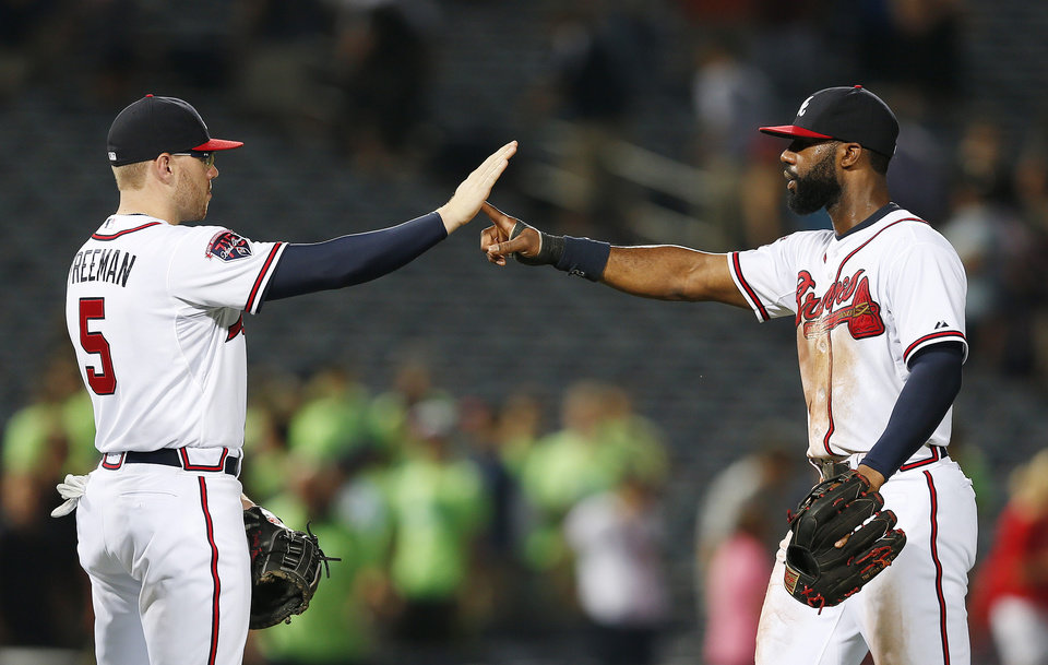Photo - Atlanta Braves' Freddie Freeman, left, and Jason Heyward celebrate after defeating the Miami Marlins 6-1 in baseball game in Atlanta, Wednesday, July 23, 2014. (AP Photo)