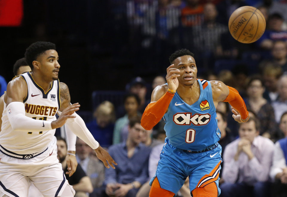 Photo - Denver Nuggets guard Gary Harris, left, and Oklahoma City Thunder guard Russell Westbrook (0) chase a loose ball in the first half of an NBA basketball game Friday, March 29, 2019, in Oklahoma City. (AP Photo/Sue Ogrocki)