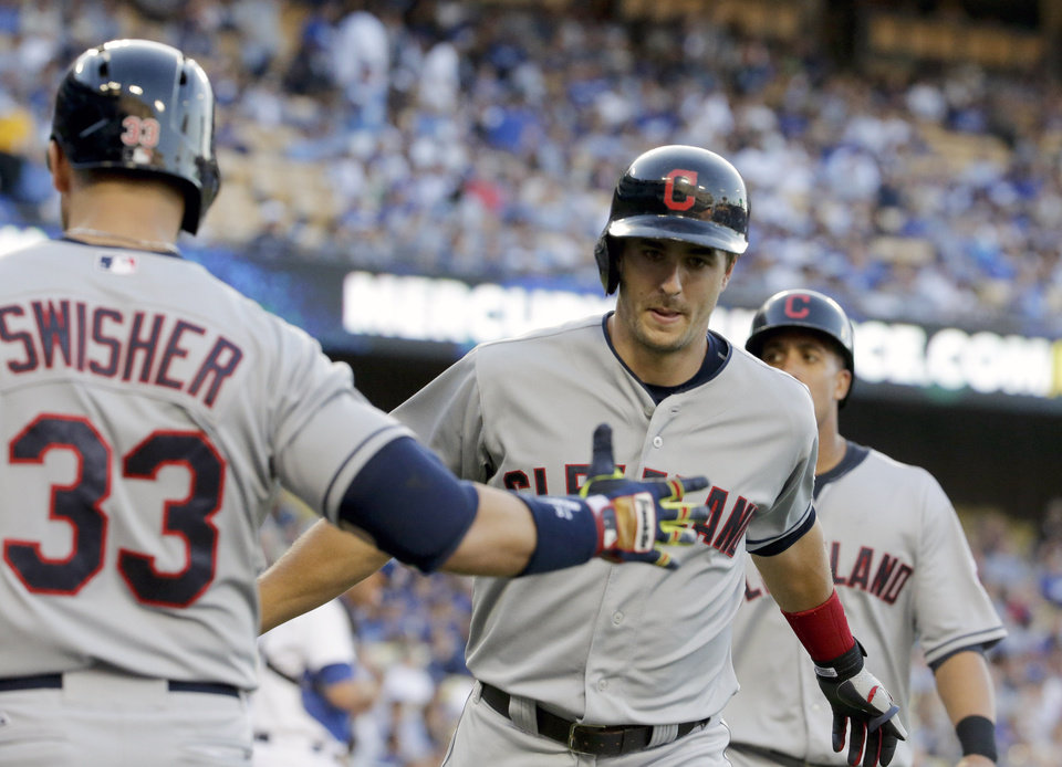 Photo - Cleveland Indians' Lonnie Chisenhall, right, celebrates his two run home run with Nick Swisher during the first inning of a baseball game in Los Angeles, Tuesday, July 1, 2014. (AP Photo/Chris Carlson)