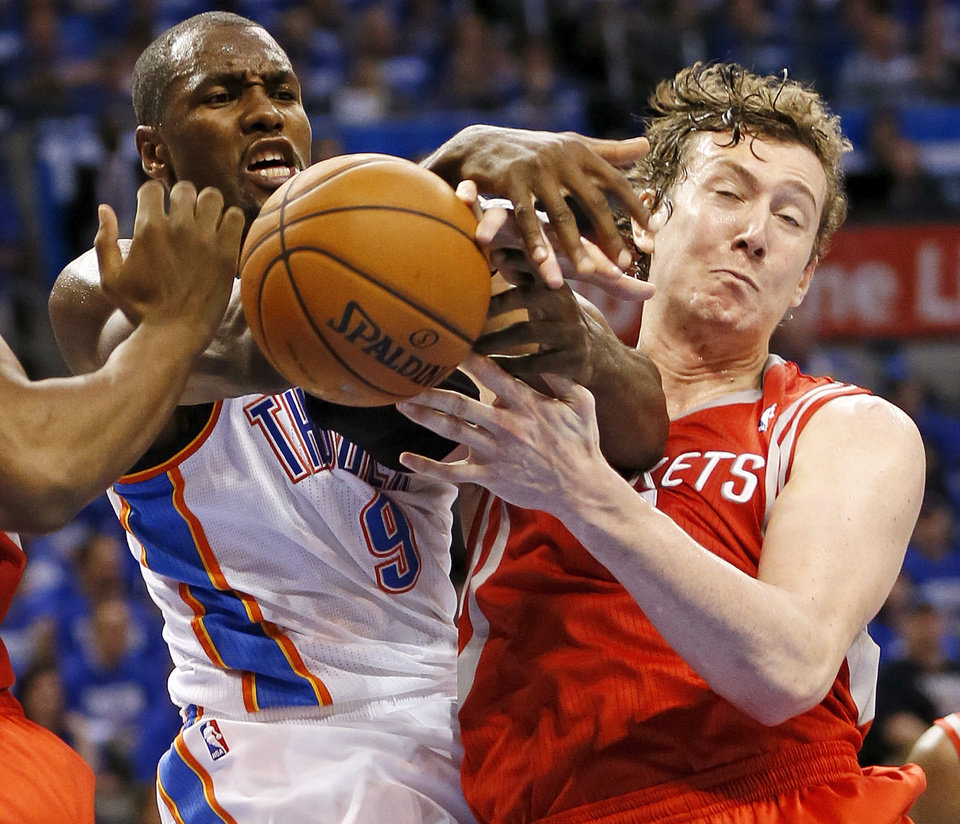 Photo - Oklahoma City's Serge Ibaka (9) and Houston's Omer Asik (3) battle for a rebound during Game 1 in the first round of the NBA playoffs between the Oklahoma City Thunder and the Houston Rockets at Chesapeake Energy Arena in Oklahoma City, Sunday, April 21, 2013. Oklahoma City won, 120-91. Photo by Nate Billings, The Oklahoman