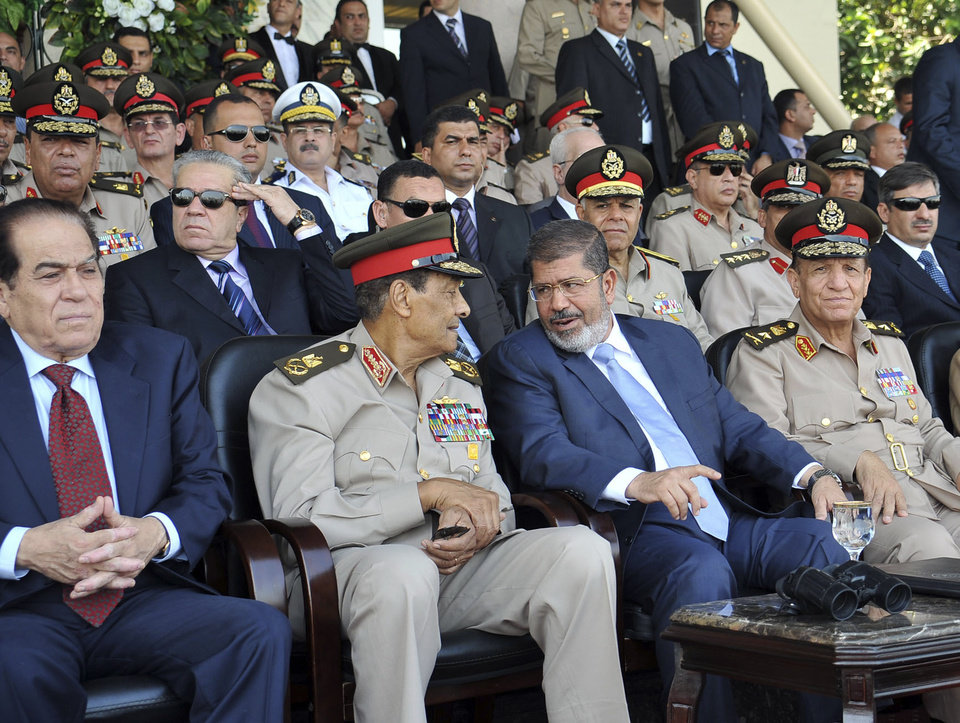 In this photo released by the office of the Egyptian Presidency, President Mohammed Morsi, second from right, talks with Field Marshal Hussein Tantawi, second left, as they attend a military graduation ceremony with Prime Minister Kamal el-Ganzouri, left, and Chief of Staff Sami Anan, right, in Cairo, Egypt, Tuesday, July 17, 2012. Egypt�s President Mohammed Morsi hailed the Egyptian army and its commanders at a time the newly elected Islamist president and the military council, which took power after ouster of Hosni Mubarak last year, are in mid of power struggle. (AP Photo/Sheriff Abd El Minoem, Egyptian Presidency)