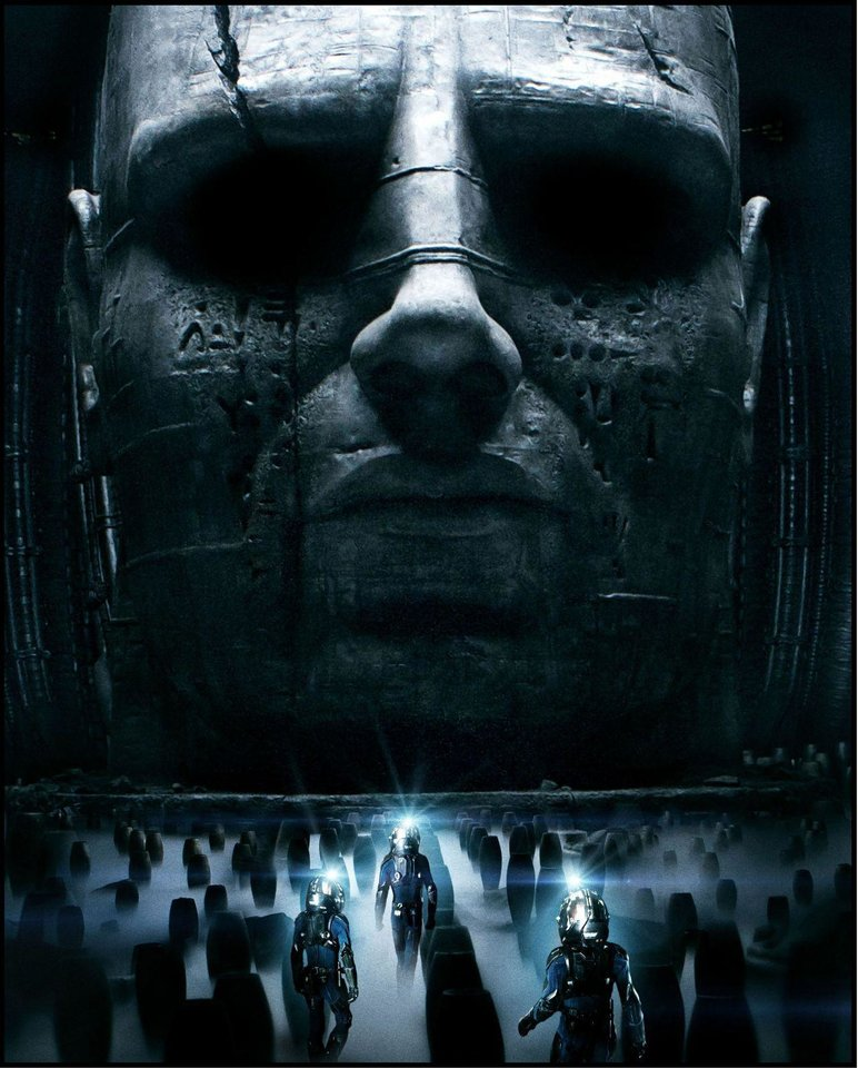Photo - A monolithic figure towers over the explorers of a distant planet in Ridley Scott's