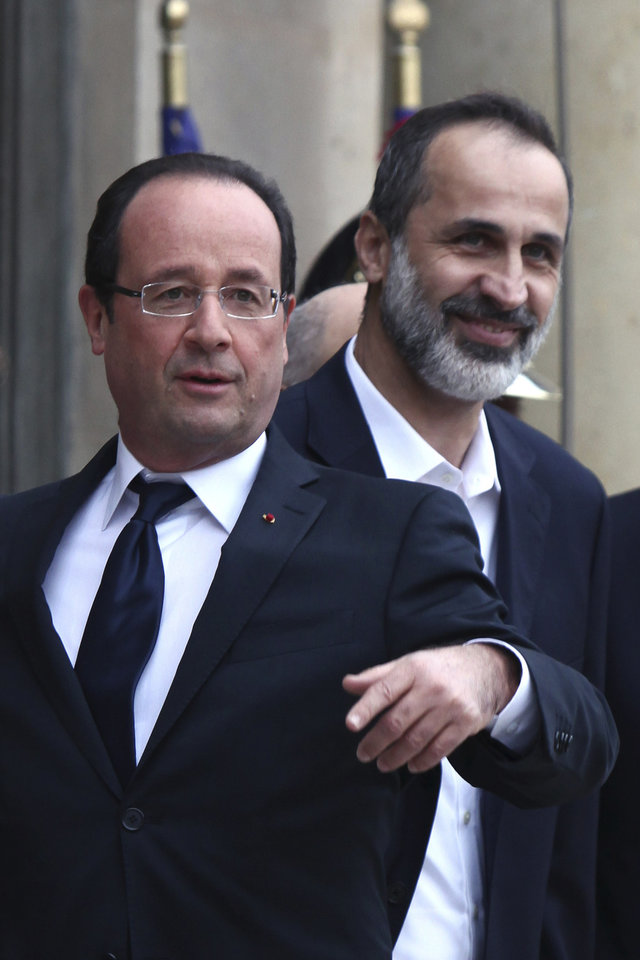 Photo -   French President Francois Hollande, left, gestures as he welcomes head of the new Syrian National Coalition for Opposition and Revolutionary Forces Mouaz al-Khatib, right, prior to a meeting, at the Elysee Palace, in Paris, Saturday, Nov. 17, 2012. France has taken a leading role among Western countries in supporting Syria's rebels. On Tuesday, it became the first Western nation to formally recognize Syria's newly formed opposition coalition as the sole legitimate representative of the Syrian people. (AP Photo/Thibault Camus)