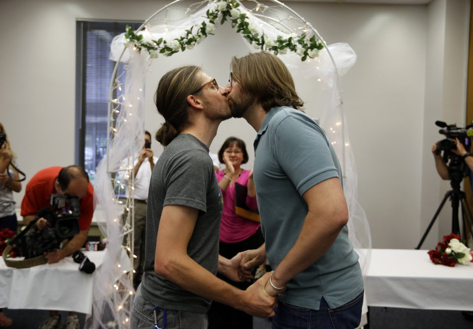 Photo - Jake Miller, 30, and Craig Bowen, 35, right, kiss after being married by Marion County Clerk Beth White, center, in Indianapolis, Wednesday, June 25, 2014. A federal judge struck down Indiana's ban on same-sex marriage Wednesday in a ruling that immediately allowed gay couples to wed. (AP Photo/Michael Conroy)