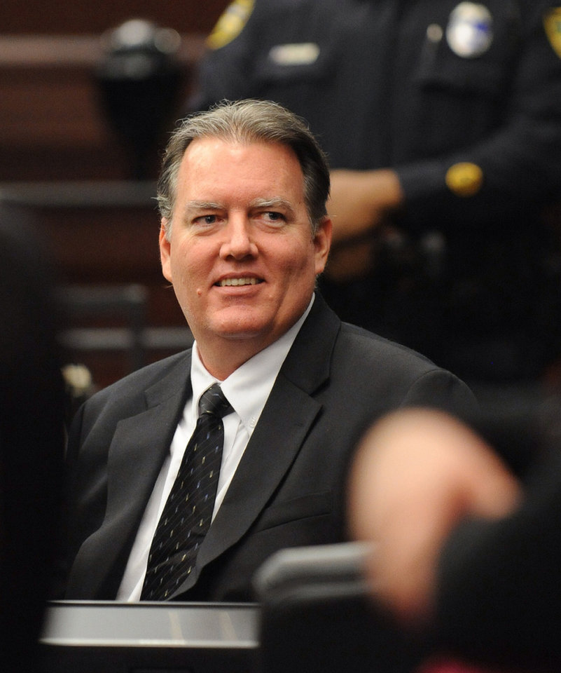 Photo - Michael Dunn smiles at his parents during a break in his trial in Jacksonville, Fla. Wednesday, Feb. 12, 2014.   Dunn is charged in the shooting death of Jordan Davis in November 2012. (The Florida Times-Union, Bob Mack, Pool)