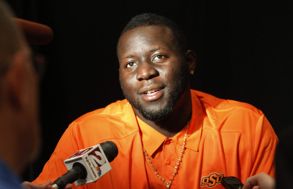 Oklahoma State defensive tackle Calvin Barnett conducts interviews during the Big 12 Conference Football Media Days Monday, July 22, 2013 in Dallas.  (AP Photo/Tim Sharp)