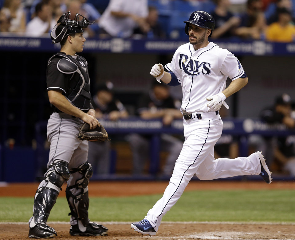 Photo - Tampa Bay Rays' Matt Joyce, right, scores in front of Miami Marlins catcher Jacob Realmuto on an RBI single by Jerry Sands during the sixth inning of an interleague baseball game Thursday, June 5, 2014, in St. Petersburg, Fla. (AP Photo/Chris O'Meara)