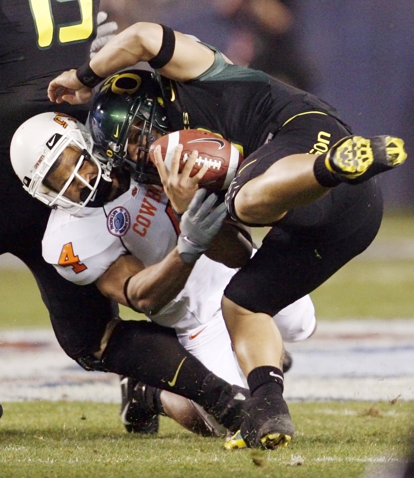 Photo - OSU's Patrick Lavine (4) sacks Oregon quarterback Jeremiah Masoli (2) in the first quarter of the Holiday Bowl college football game between Oklahoma State and Oregon at Qualcomm Stadium in San Diego, Tuesday, Dec. 30, 2008. PHOTO BY NATE BILLINGS, THE OKLAHOMAN