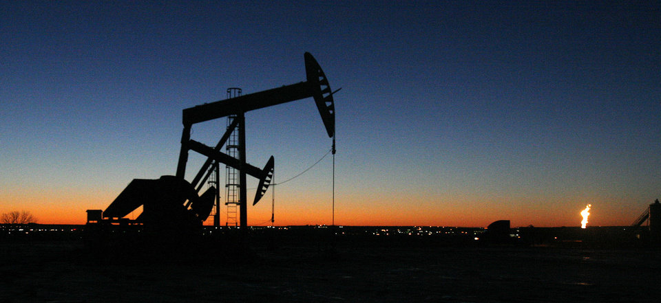 Photo - FILE - In this Feb. 25, 2014 file photo, the lights of Williston, N.D. shine in the background of oil pumps. Williston is the hub of North Dakota's oil boom. The AFL-CIO, the nation's largest labor federation, says the death rate for oil, gas and mining workers in North Dakota was more than six times the national average in 2012. It says the state had a fatality rate of 104 per 100,000 workers in those industries. (AP Photo/Martha Irvine, File)