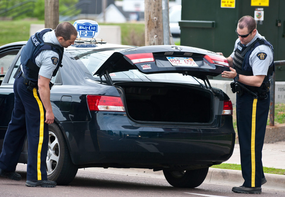 Photo - Royal Canadian Mounted Police check the trunk of a taxi at a roadblock in Moncton, New Brunswick on Thursday, June 5, 2014. A RCMP manhunt for a gunman suspected of killing three Mounties and wounding two others passed the 12-hour mark Thursday in Moncton as a large section of the New Brunswick city was under a virtual siege. (AP Photo/The Canadian Press, Marc Grandmaison)