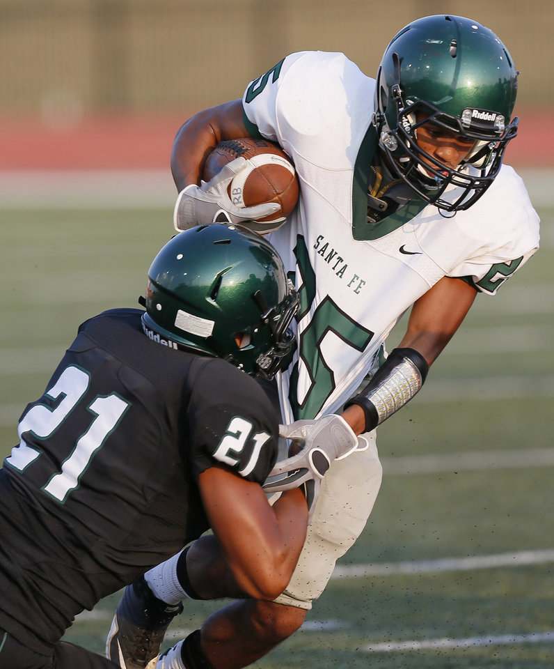 Photo - Norman North's DJ Hicks (21) brings down Edmond Santa Fe's Dale Jefferson (25) during a high school football scrimmage at Moore Stadium between Edmond Santa Fe and Norman North in Moore, Okla., Thursday, Aug. 16, 2012. Photo by Nate Billings, The Oklahoman