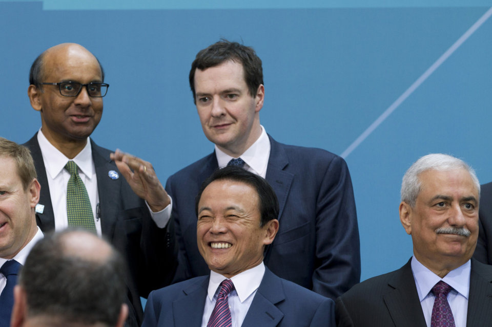 Photo - Singapore Finance Minister Tharman Shanmugaratnam speaks with Great Britain Chancellor of the Exchequer George Osborne during the G-20 finance ministers and central bank governors group photo on the sidelines of their meeting at World Bank Group-International Monetary Fund Spring Meetings in Washington, Friday, April 11, 2014.  Japanese Finance Minister Taro Aso is at center, Saudi Arabian Finance Minister Ibrahim Al-Assaf is at right.  (AP Photo/Jose Luis Magana)