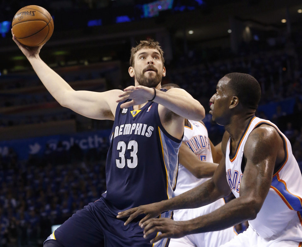 Photo - Memphis Grizzlies center Marc Gasol (33) shoots over Oklahoma City Thunder center Kendrick Perkins (5) during the second quarter of Game 1 of their Western Conference Semifinals NBA basketball playoff series in Oklahoma City, Sunday, May 5, 2013. (AP Photo/Sue Ogrocki)