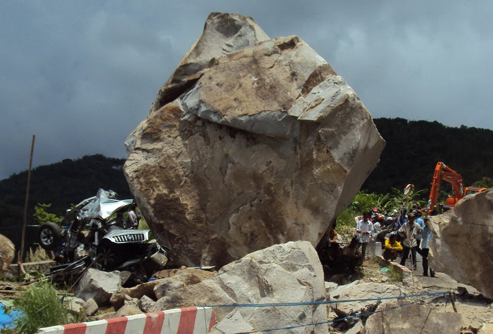 In this May 6, 2012 photo, villagers look at the wreckage of car, left, which was destroyed when a huge boulder fell from a mountain, killing six people inside the car and injuring two others in southern province of An Giang, Vietnam. The victims were on a religious pilgrimage. (AP Photo/Tuoi Tre Newspaper, Duc Vinh)