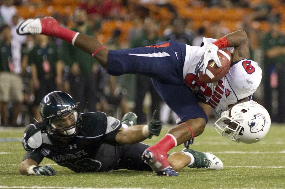 Hawaii wide receiver Scott Harding (29) trips up South Alabama cornerback Tyrell Pearson (9) after Pearson intercepts a Hawaii pass in the third quarter of an NCAA college football game Saturday, Dec. 1, 2012, in Honolulu. (AP Photo/Eugene Tanner)