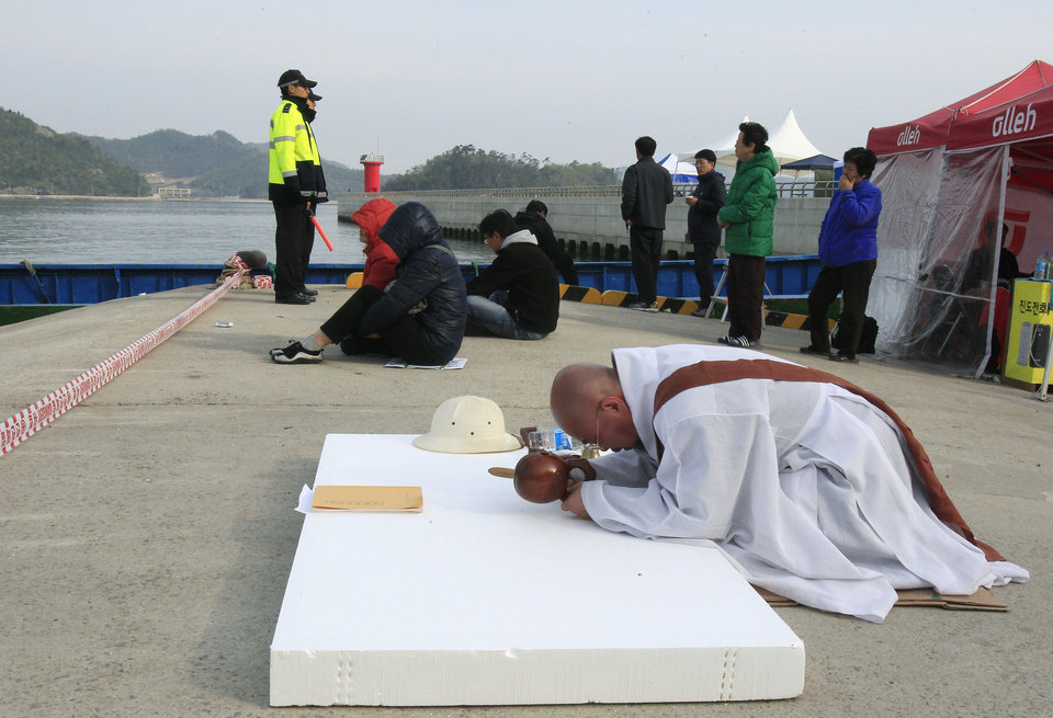 Photo - A Buddhist monks prays for the safe return of passengers of the sunken Sewol ferry at a port in Jindo, South Korea, Tuesday, April 22, 2014. As divers continue to search the interior of the sunken ferry, the number of confirmed deaths has risen, with about 220 other people still missing.  (AP Photo/Ahn Young-joon)