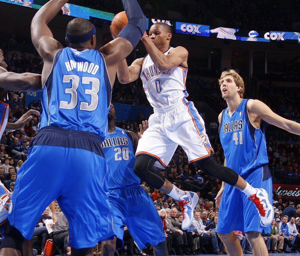 Photo - Oklahoma City's' Russell Westbrook (0) goes between Dallas' Brendan Haywood (33) and Dirk Nowitzki (41) during a preseason NBA game between the Oklahoma City Thunder and the Dallas Mavericks at Chesapeake Energy Arena in Oklahoma City, Tuesday, Dec. 20, 2011. Photo by Bryan Terry, The Oklahoman