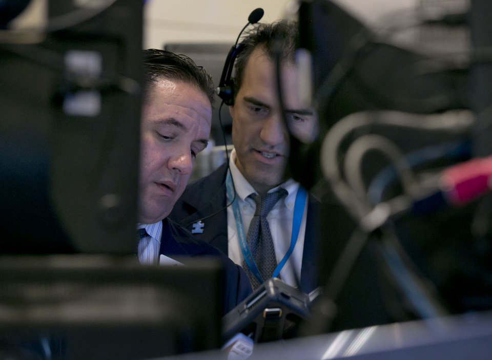 Photo - Traders Tommy Kalikas, left, and Gregory Rowe consult their handheld devices on the floor of the New York Stock Exchange, Tuesday, Aug. 5, 2014. The stock market fell to its lowest point since May as traders worried that tensions between Russia and Ukraine could flare up. (AP Photo/Richard Drew)