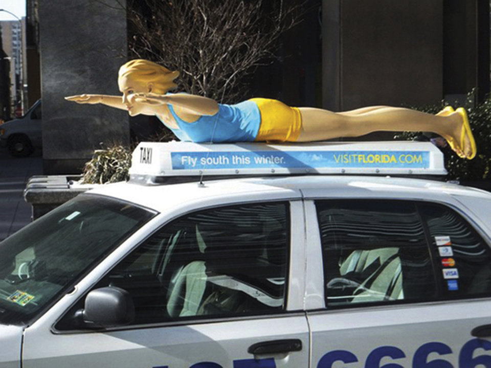Photo - This Feb. 18, 2014 photo provided by VISIT FLORIDA shows a fiberglass mannequin atop a taxi in Philadelphia promoting the warmth of Florida as winter rolls on in the northern parts of the country with the return of yet another polar vortex like storm system. Florida resorts and other tourist operations have been fueling this with email and other ad campaigns dangling a little sunshine and beach scenes in front of us. (AP Photo/Courtesy of VISIT FLORIDA)