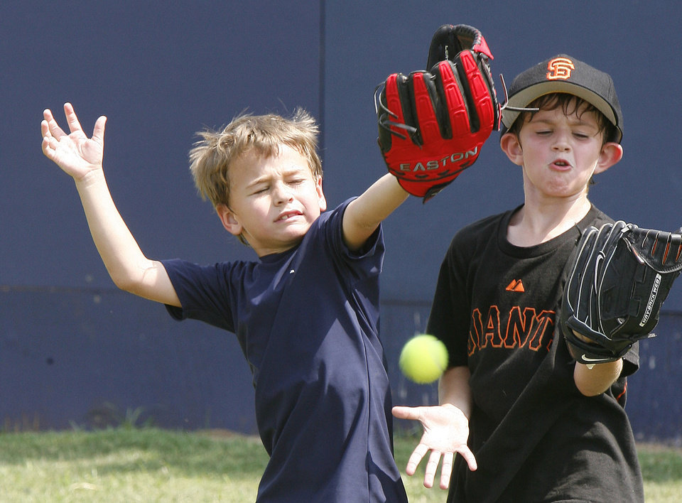 Seven-year-olds Matt Minielly (left) and Tucker Resolute practice catching a fly ball, as the University of Central Oklahoma hosts a baseball camp on their campus in Edmond, OK, Tuesday, June 8, 2010. Photo by Paul Hellstern, The Oklahoman
