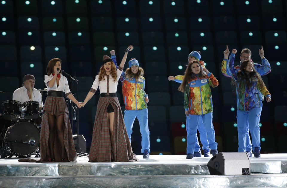 Photo - Russian duo t.A.T.u. Lena Katina, third from left, and Yulia Volkova, second from left,  perform on stage before the opening ceremony of the 2014 Winter Olympics in Sochi, Russia, Friday, Feb. 7, 2014. (AP Photo/Mark Humphrey)