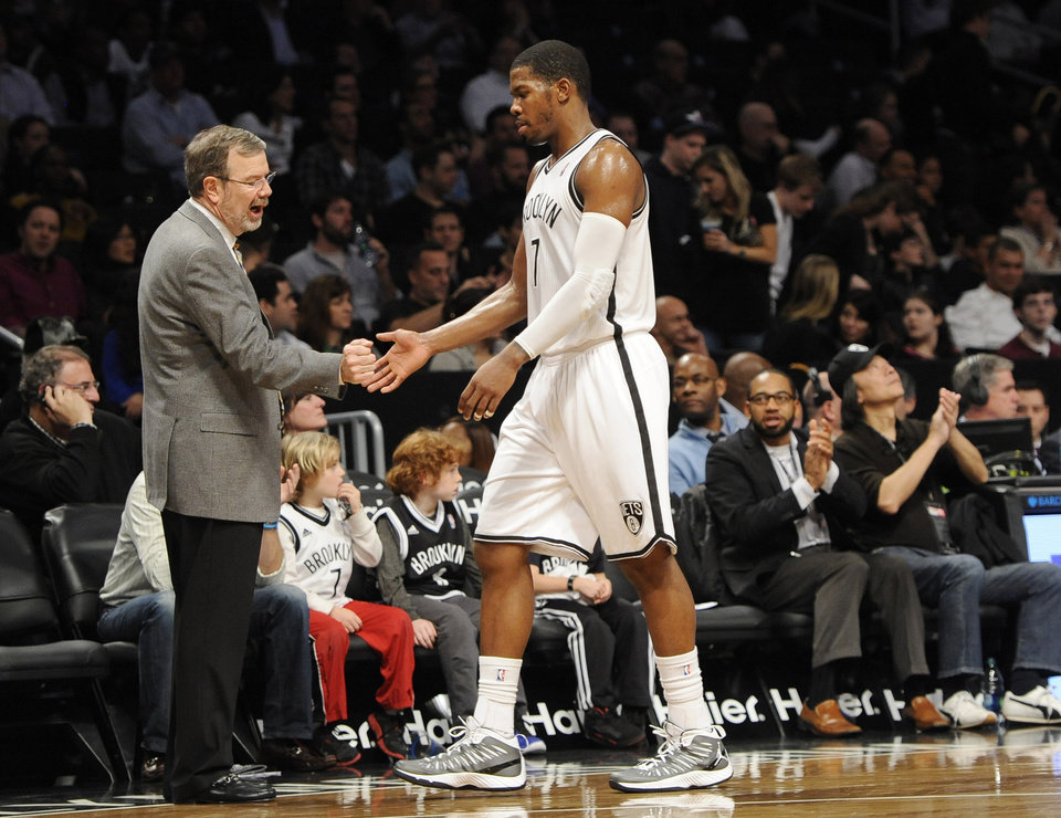 Photo - Brooklyn Nets interim head coach P.J. Carlesimo shakes hands with Joe Johnson (7) as he comes off the court in the second half of an NBA basketball game against the Phoenix Suns on Friday, Jan., 11, 2013 at Barclays Center in New York. Johnson scored 19 points in the Nets 99-79 win. (AP Photo/Kathy Kmonicek)