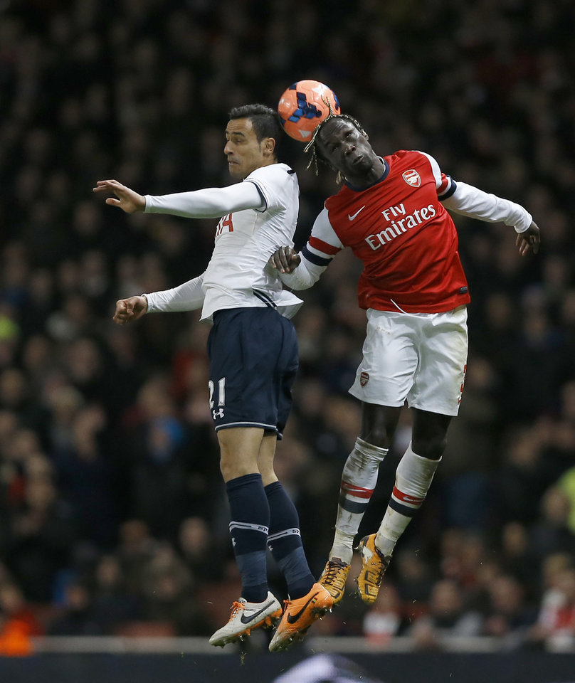 Photo - Arsenal's  Bacary Sanga, right jumps for the ball with Tottenham's Nacer Chadli during the English FA Cup third round soccer match between Arsenal and Tottenham Hotspur at the Emirates Stadium in London, Saturday, Jan. 4, 2014. (AP Photo/Kirsty Wigglesworth)