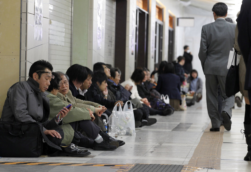 Photo - Stranded commuters sit inside Tokyo railway station as train services are suspended due to a powerful earthquake in Tokyo Friday, March 11, 2011. The largest earthquake in Japan's recorded history slammed the eastern coasts Friday. (AP Photo/Hiro Komae) ORG XMIT: TTX102