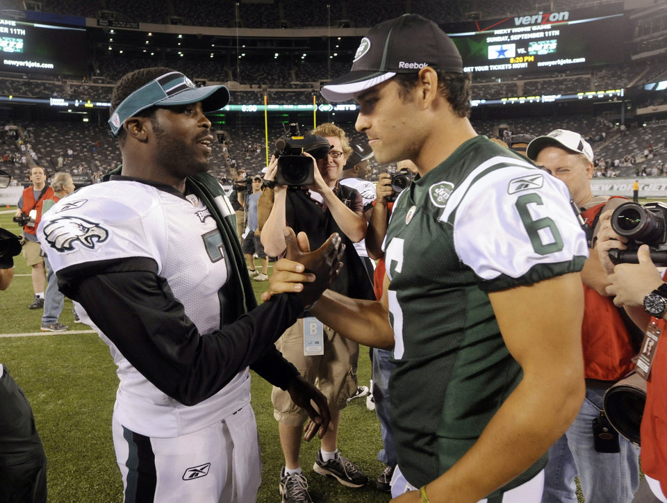 Photo - FILE - In this Sept. 1, 2011, file photo, Philadelphia Eagles' Michael Vick, left, greets New York Jets' Mark Sanchez after a preseason NFL football game in East Rutherford, N.J. The  Jets signed Vick and released Sanchez on Friday, March 21, 2014. Vick was a free agent after spending the last five seasons with the Phialdelphia Eagles.  (AP Photo/Bill Kostroun, File)
