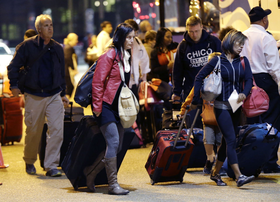 Photo - Passengers from the disabled Carnival Triumph cruise ship arrive by bus at the Hilton Riverside Hotel in New Orleans, Friday, Feb. 15, 2013. The ship had been idled for nearly a week in the Gulf of Mexico following an engine room fire. (AP Photo/Gerald Herbert)
