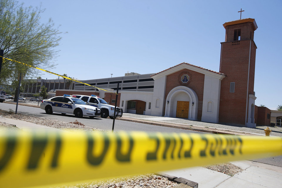 Photo - Phoenix police were still on the scene after a Wednesday evening attack left a priest shot and killed and another injured at the Roman Catholic church the Mother of Mercy Mission on Thursday, June 12, 2014, in Phoenix.  Police have no suspects at this point, but they are canvassing the neighborhood and going over physical evidence from the scene. (AP Photo/Ross D. Franklin)